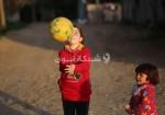 فتاة تلعب الكرة في مخيم بغزة