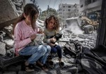طفلتان فلسطينتان على أنقاض بيتهما المهدّم